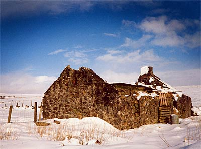 Photo showing a roofless cottage in the snow under a crisp blue sky