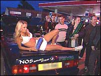 Group of people gathered around a woman laid on a car