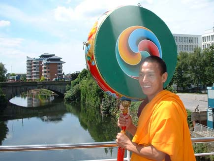 A smiling monk crosses the River Irwell with a large, brightly-painted instrument that looks somewhat like a tambourine or drum, somewhat like a giant lollipop