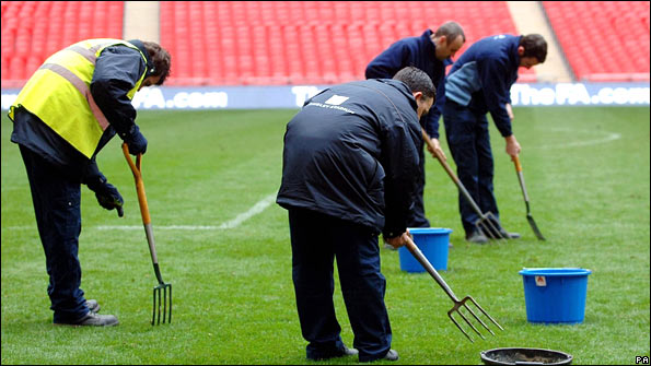 Groundsmen work on Wembley pitch