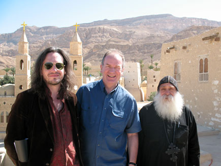 Nicholas Buxton, Stephen Shipley and Father Ruwais smile at the camera among the buildings of St Antony's Monastery with the Egyptian mountains in the background
