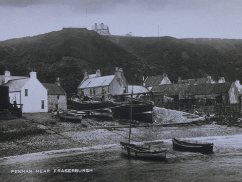Black and white view showing small and large fishing boats pulled up onto the shore with cottages beneath tall cliffs behind.