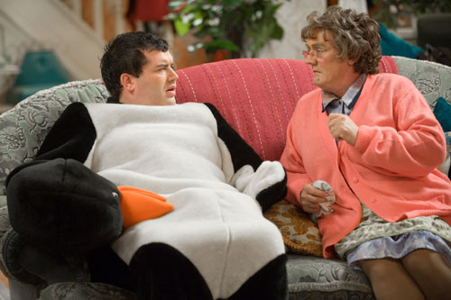 Mrs Brown, played by Brendan O'Carroll, sits on the sofa next to Dermot Brown, played by Paddy Houlihan, who is dressed as a penguin.