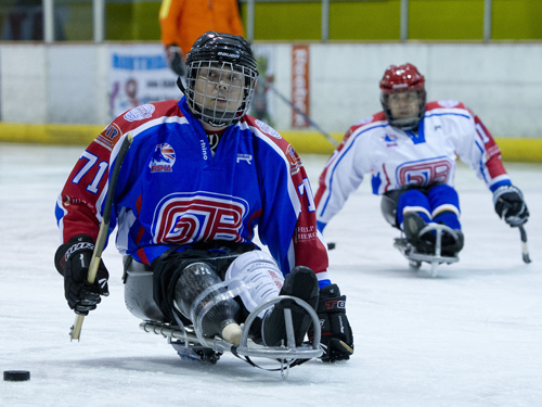 GB sledge hockey players preparing to hit the puck