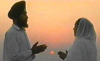 A man and woman praying in white garments at sunrise