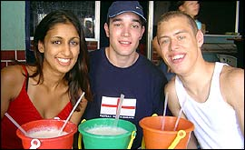 Sonya, Dan and James drink juice from beach buckets