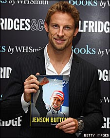 Jenson Button poses with a copy of his diary of his championship year