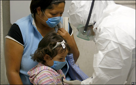 A doctor wearing protective gear examines a child in an area set up to treat people suspected of being sick with swine flu at the Naval hospital in Mexico City