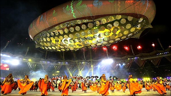Entertainers perform underneath a giant aerostat at the Jawaharlal Nehru Stadium