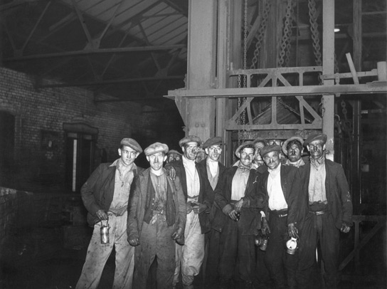 Miners pose outside the pit cage, which takes them to and from the coal face, after a shift underground