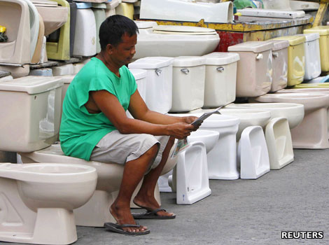 A Filipino man takes a seat on a second-hand toilet bowl he is selling.