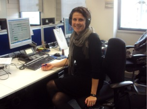 Picture of Catherine Carr at her desk at work wearing a black dress with black tights and boots.