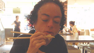 Liz Carr in Japan, trying out eating with chopsticks