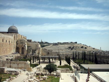 The silvery dome of the Al Aqsa mosque on the left, looking out towards the Mount of Olives in the background, with old, tumbledown walls of white stone blocks in the foreground