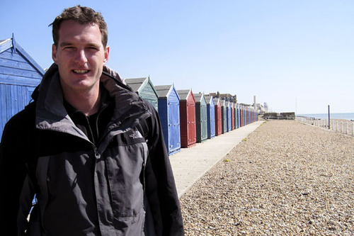 Dan Snow stands in front of multicoloured beach huts on Hastings seafront