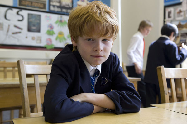 Harry, one of the pupils featured sits at a desk