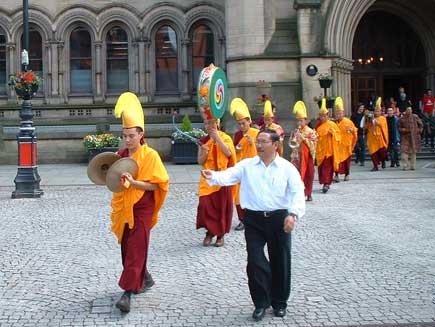 The monks leave Manchester Town Hall in procession, still wearing their full regalia. They are singing and playing cymbals and drums