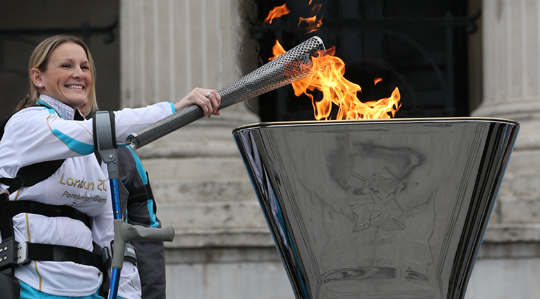 Disabled marathon runner Claire Lomas lights the Olympic cauldron for the Paralympic Games.