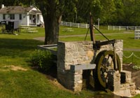 Stone waterwheel in an Amish village. A horse buggy is visible in the distance