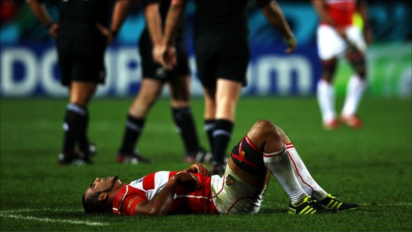 A Japan rugby player lies prostrate
