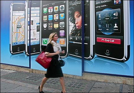 A woman walks past an iPhone advert in central London