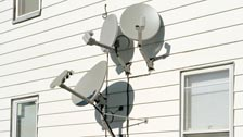 Satellite dishes on the side of a house