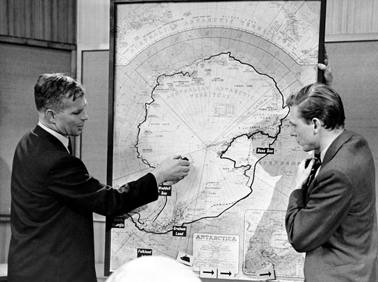 Dr Vivian Fuchs and David Attenborough look at a map of Antarctica.