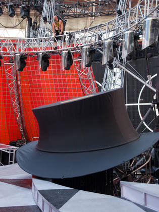 A little man in a harness looks down at a giant top hat.