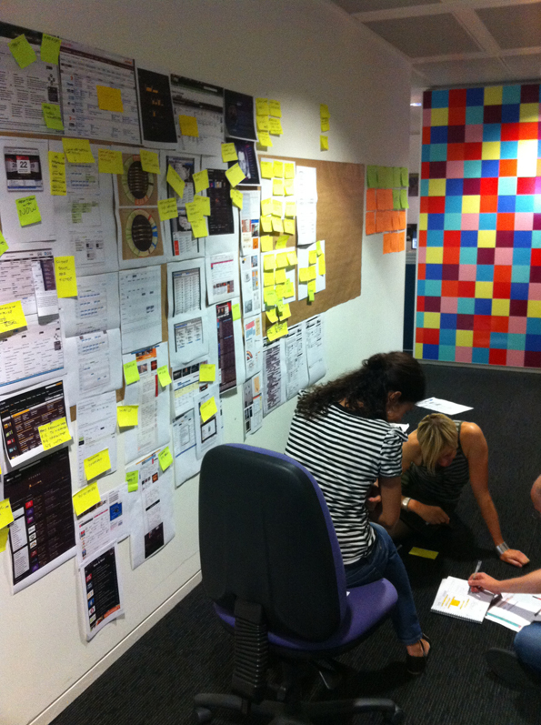 A meeting wall full of ideas and potential designs. Two people lean over a third writing in a book.