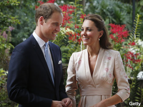 The Duke and Duchess of Cambridge smile as they look at an orchid.