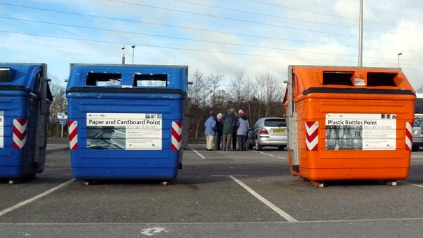 People in a car park, between recycling bins