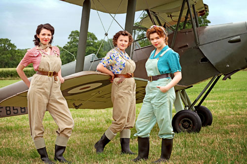 Connie, played by Seline Hizli, Joyce, played by Becci Gemmell, and Bea, played by Jo Woodcock, stand in front of a Tiger Moth plane.