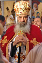 Coptic Orthodox Pope Shenouda III, bearded gentleman with cane in red and gold robe and headdress adorned with equal-armed Christian crosses