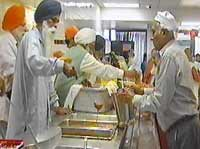 Sikh men serve food inside a Langar