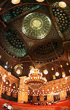 High domed roof and brightly-lit interior of a mosque