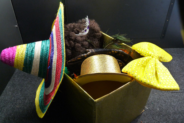 A box full of props including hats and bow-ties