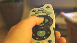 Close-up of Charlie's hand pointing the remote control at the TV