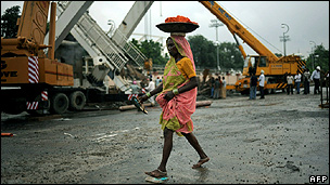 An Indian worker walks in front of a collapsed bridge next to the Jawaharlal Nehru Stadium