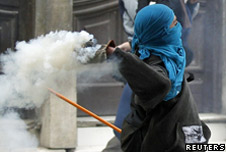 A masked student throws a tear gas canister