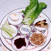 Plate with seder meal: lettuce, lamb bone, charoset, horseradish paste, celery and roast egg