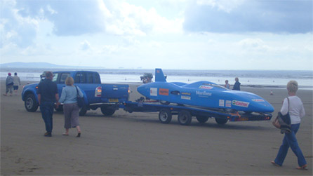 The electric car is towed off the sands for repairs. Image by Rachael Garside.