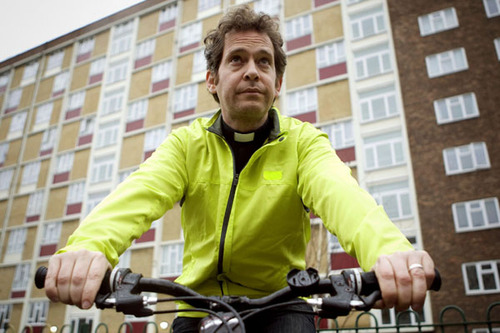 Tom Hollander as the Reverend Adam Smallbone on his bike, wearing a yellow luminous jacket