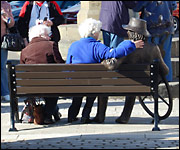 Ladies sat on bench with sculpture of Blind Jack