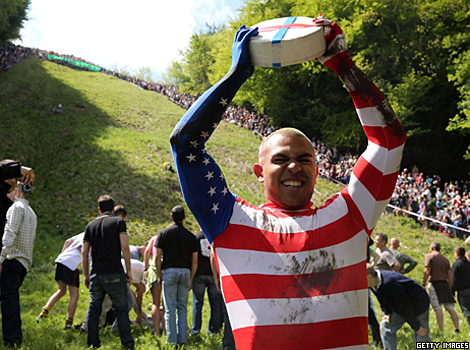 A man holds a large wheel of cheese during a cheese-rolling competition