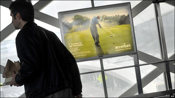 A passenger walks past an Accenture advertisement featuring Tiger Woods at San Francisco International Airport