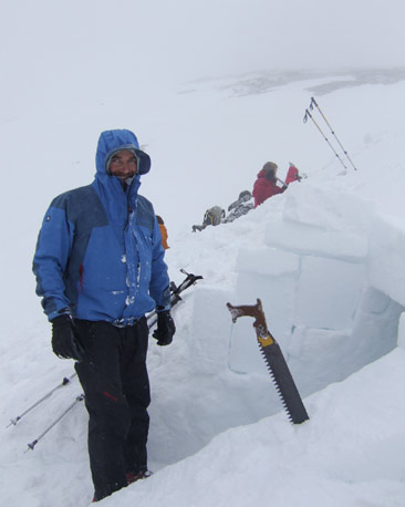 Mountaineer with snow saw, building snow-hole