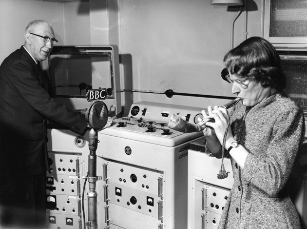 Daphne oram blowing a Mijwiz, an Arabic reed pipe, while Richard Bird records the sound on a tape machine. BBC Radiophonic Workshop, Maida Vale, 1958