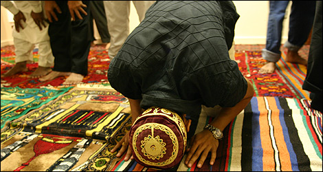 A Muslim young man kneels to the floor in prayer.