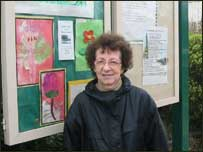 Campaigner Doris poses in front of the Handforth Community noticeboard