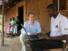 Rory Cellan-Jones and Martin Rogena outside a hut with a laptop computer